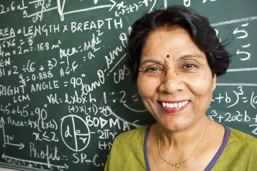 Picture of a faculty member standing in front of a chalkboard