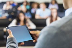 Photo of instructor in front of classroom holding a mobile tablet device - teaching to a group of students sitting at desks