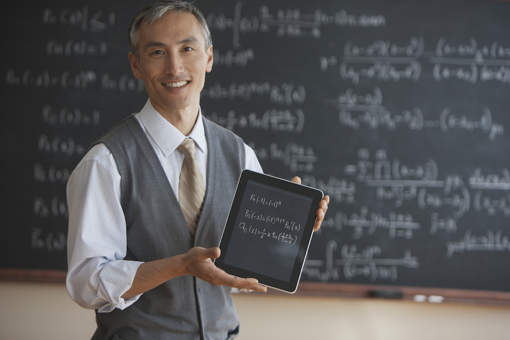 Photo of instructor standing in front of chalkboard holding a moble device