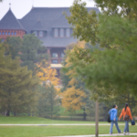Two students walking on central campus in front of Morrill Hall