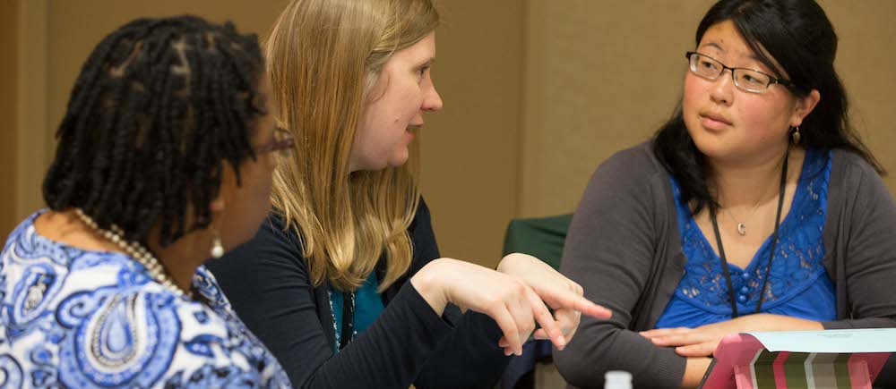 A team of instructors working with a graduate student
