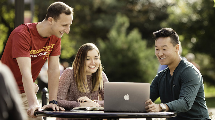 Students looking at a laptop outside of the Hub at Iowa State University