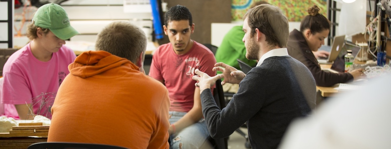 A group of students interacting with an instructor in design studio.