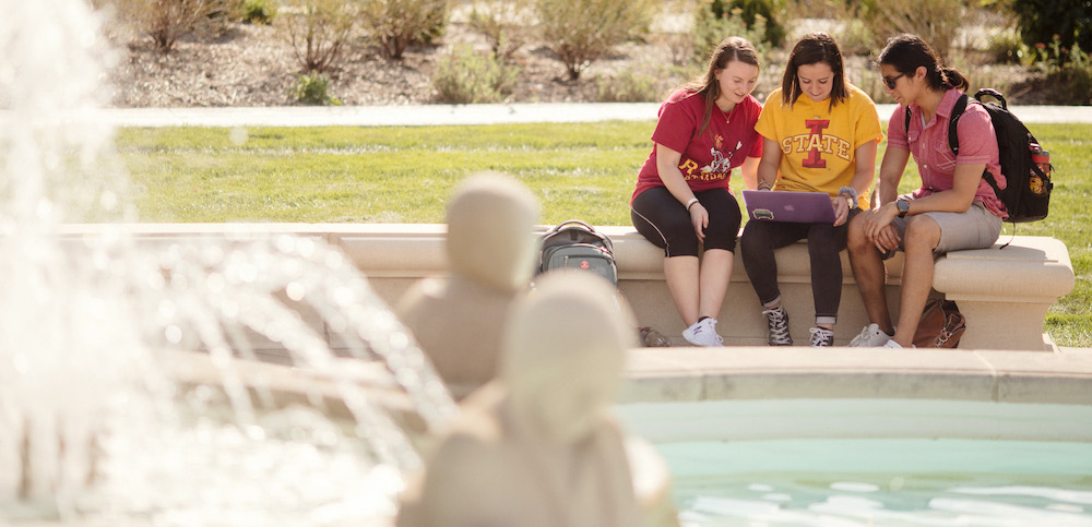 Three students sitting at the Four Seasons Fountain at Iowa State University