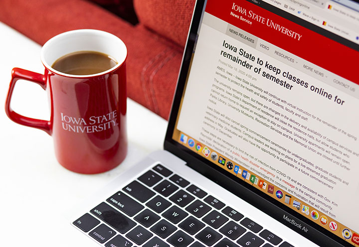 Iowa State University mug with coffee in it, and a laptop open to the ISU News page