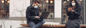 Two people wearing face protection using a laptop and a smart phone