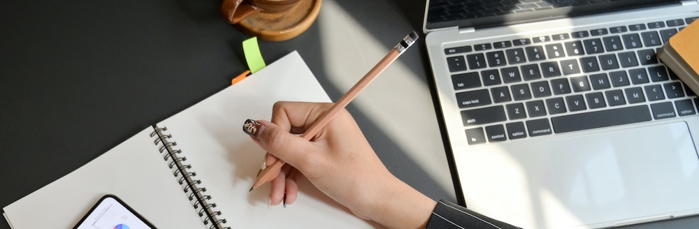 Person taking notes and using a laptop - smartphone is also on the desk