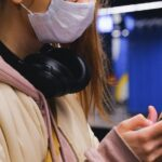 Person using a smartphone has headphones and wearing face mask