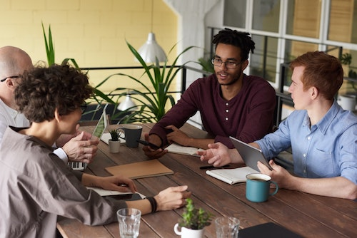 People meeting at a table - some with laptop or smart device